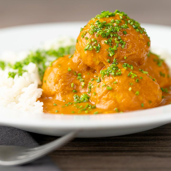 Square image of a chicken kofta or meatball curry in a masala sauce with snipped chives and basmati rice