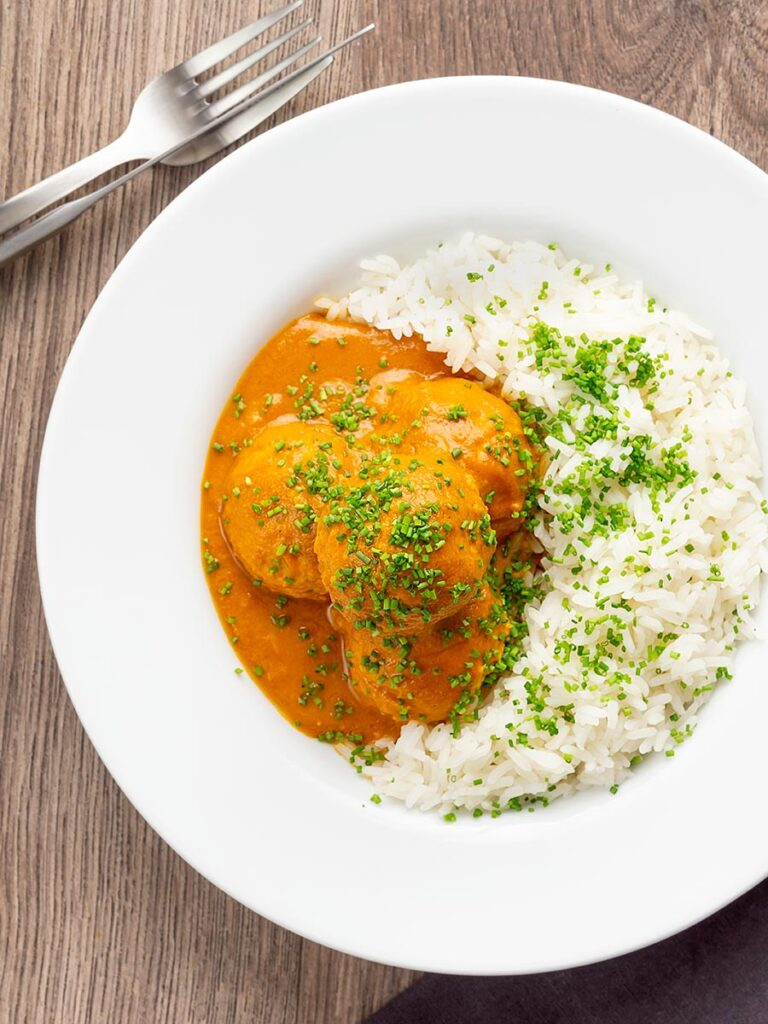 Portrait overhead image of a chicken kofta or meatball curry in a masala sauce with snipped chives