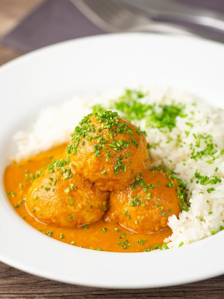 Portrait image of a chicken kofta or meatball curry in a masala sauce with snipped chives