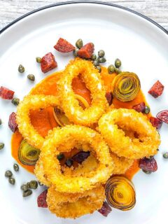 Portrait overhead image of crispy fried calamari rings that are breaded and served with romesco sauce, salami leeks, and capers