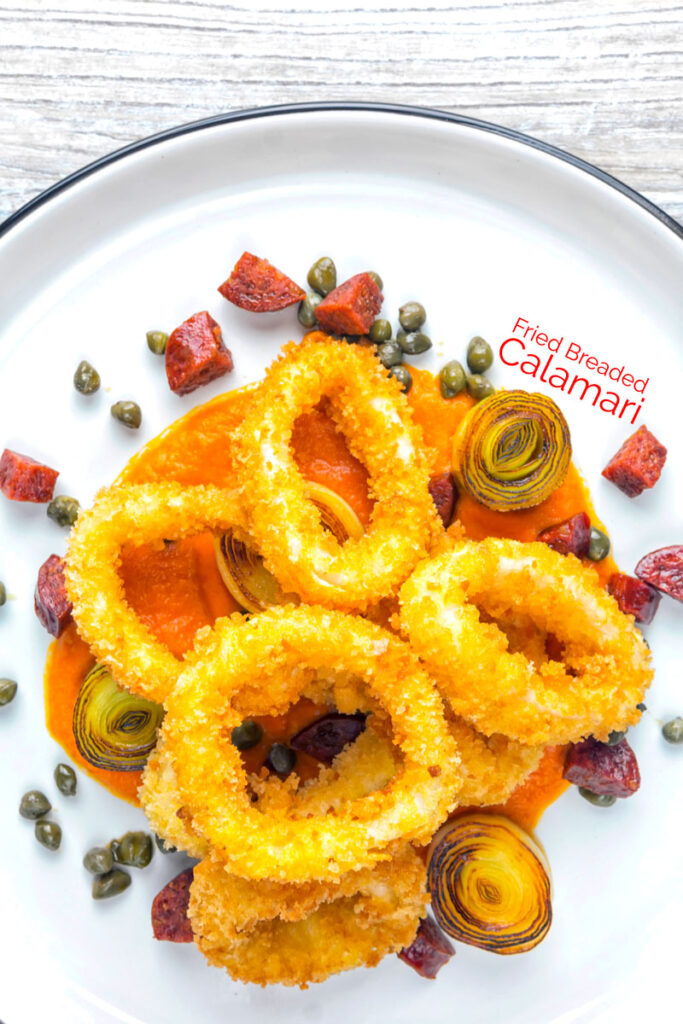 Portrait overhead image of crispy fried calamari rings that are breaded and served with romesco sauce, salami leeks, and capers with text overlay
