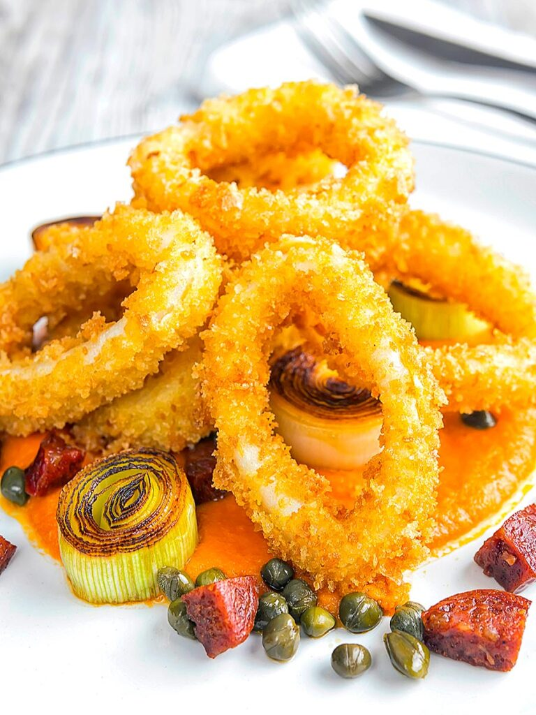 Portrait image of crispy fried calamari rings that are breaded and served with romesco sauce, salami, leeks, and capers