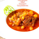 Portrait image of a Traditional Hungarian beef goulash or gulyasleves with handmade csipetke (pasta) with text overlay