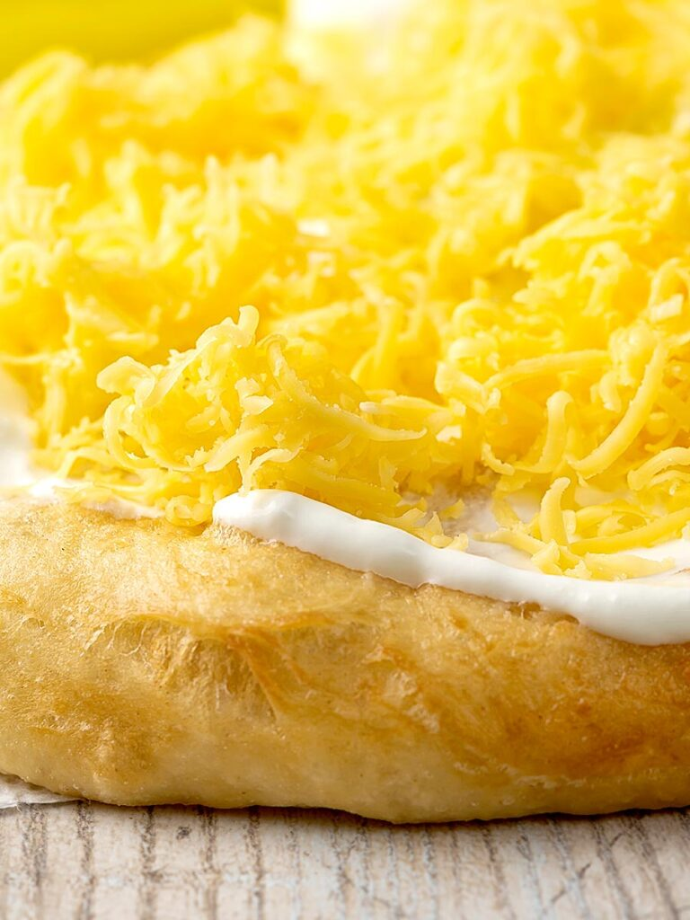 Portrait close up image of Hungarian fried bread or langos topped with sour cream and cheese