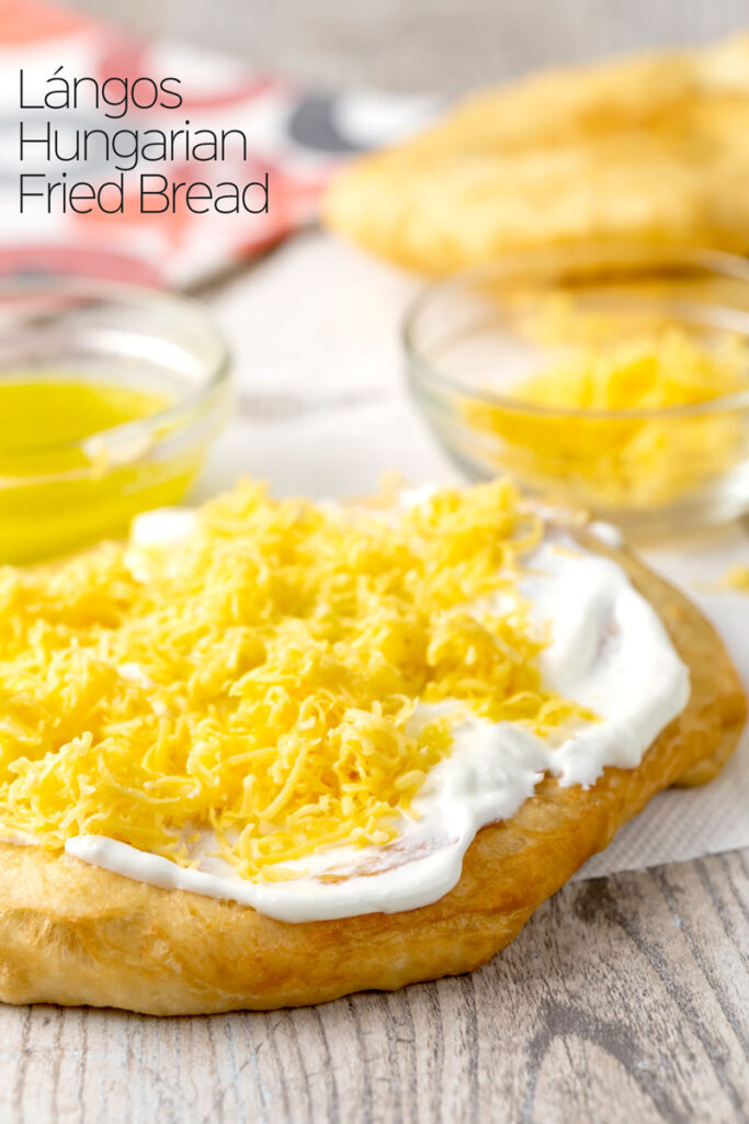 Portrait image of Hungarian fried bread or Langos topped with sour cream, cheese and garlic oil with text overlay