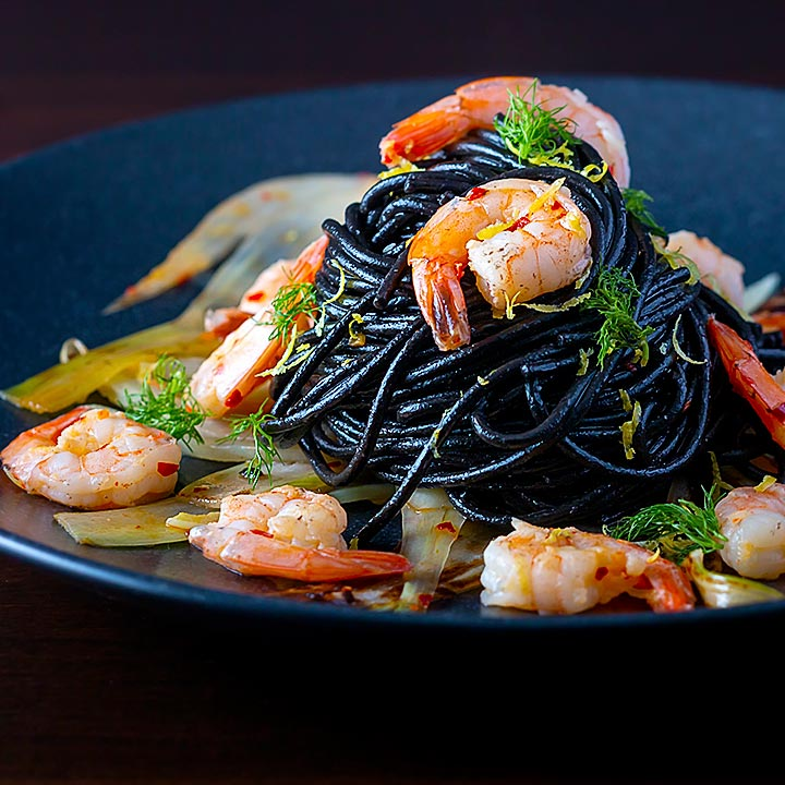 Square image of a squid ink pasta served with prawns, fennel, chilli flakes and lemon zest on a black plate
