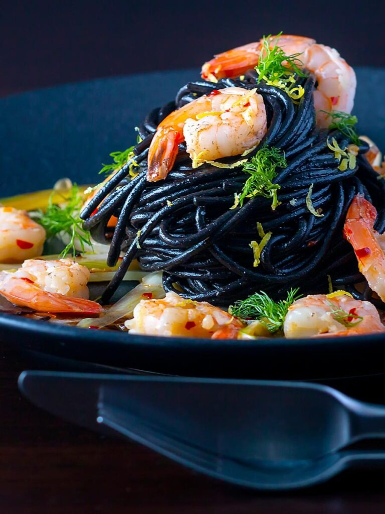 Portrait image of a squid ink pasta served with prawns, fennel, chilli flakes and lemon zest on a black plate