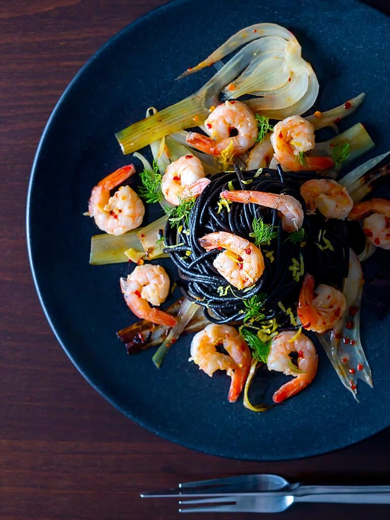 Portrait overhead image of a squid ink pasta served with prawns, fennel, chilli flakes and lemon zest on a black plate