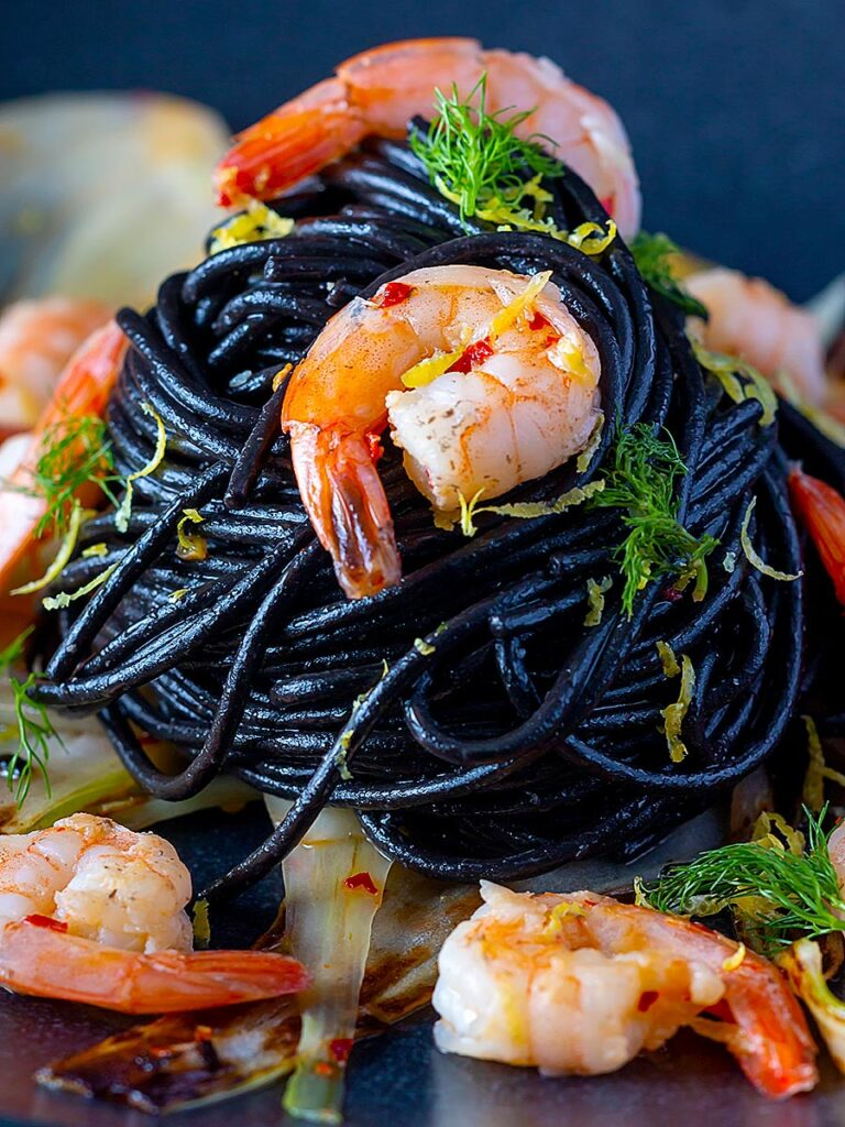 Portrait close up image of a squid ink pasta served with prawns, fennel, chilli flakes and lemon zest on a black plate