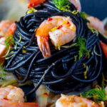 Portrait close up image of a squid ink pasta served with prawns, fennel, chilli flakes and lemon zest with text overlay