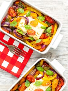 Portrait image of Mediterranean baked feta cheese with tomatoes and peppers served in a white gratin bowl