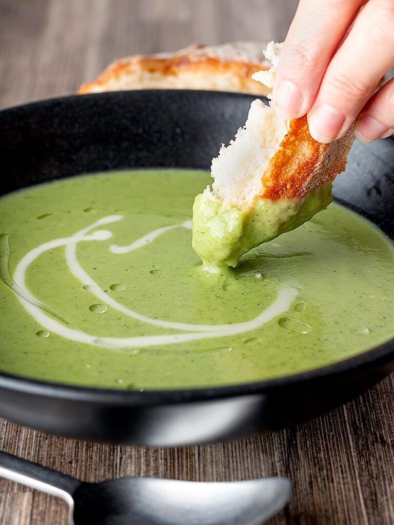 Portrait image of bread being dipped into a creamy broccoli and stilton soup