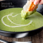 Portrait image of bread being dipped into a creamy broccoli and stilton soup with a text overlay