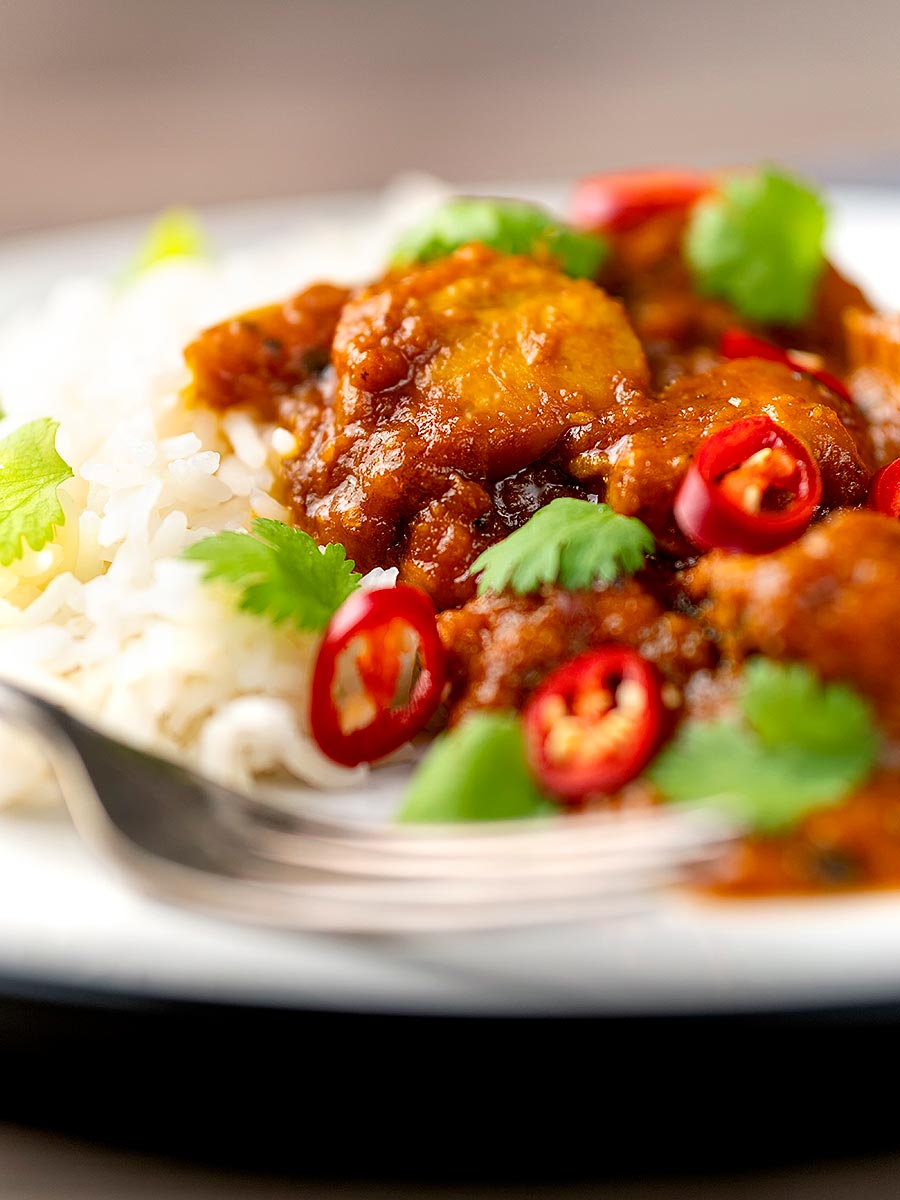Portrait close up image of a chicken pathia or patia curry served on a plate with rice, chilli slices and fresh coriander