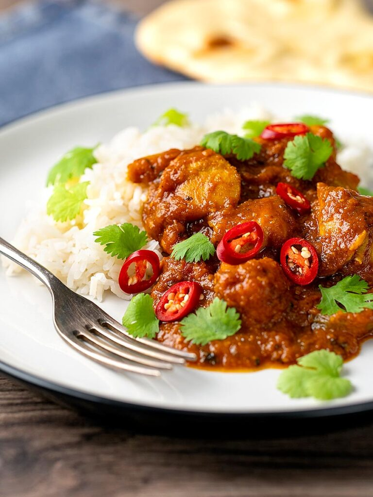 Portrait image of a chicken pathia or patia curry served on a plate with rice, chilli slices and fresh coriander