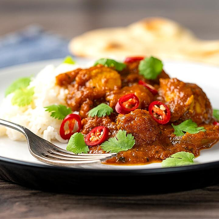 Square image of a chicken pathia or patia curry served on a plate with rice, chilli slices and fresh coriander