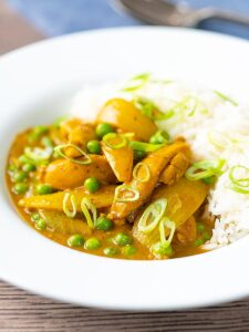 Portrait image of a takeaway style Chinese chicken curry with peas and onions served with white rice
