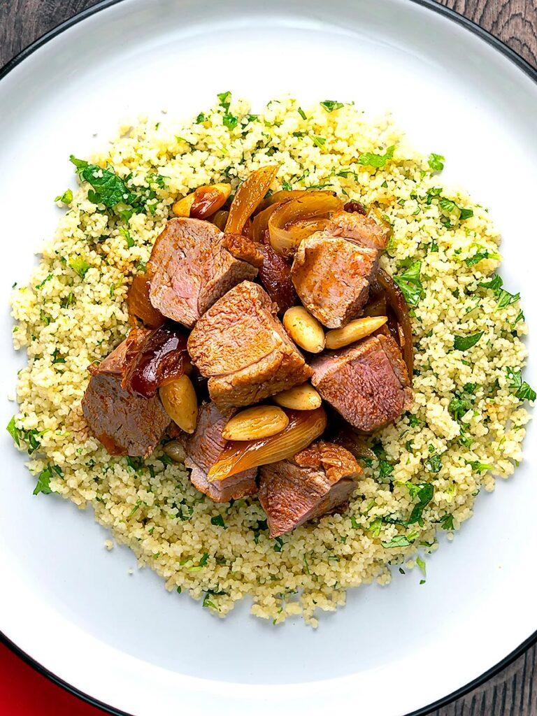 Portrait overhead image of a duck breast tagine with dates and almonds served on a bed of buttered couscous