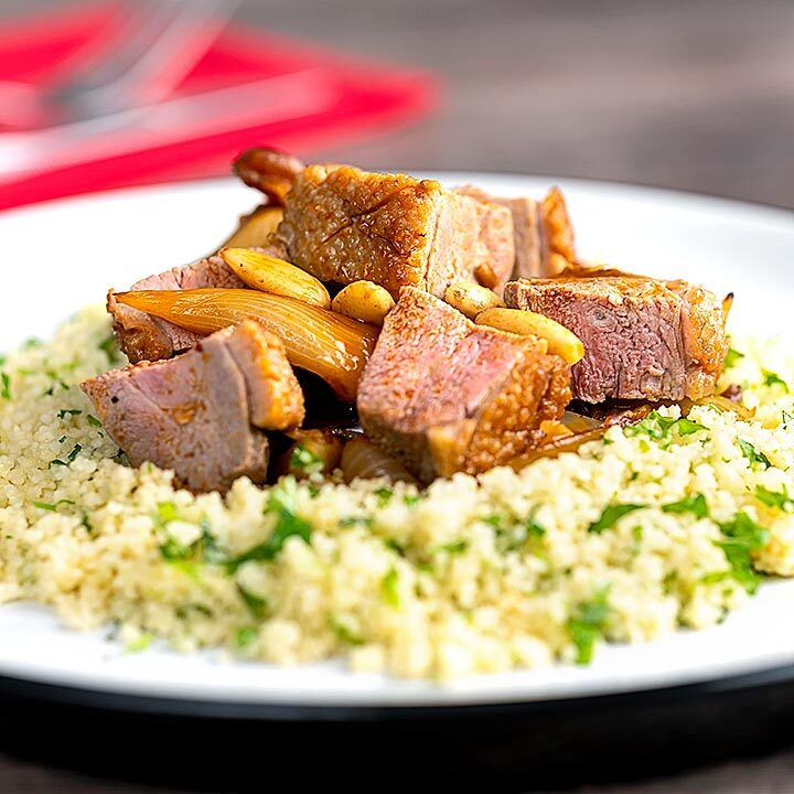 Square image of a duck breast tagine with dates and almonds served on a bed of buttered couscous
