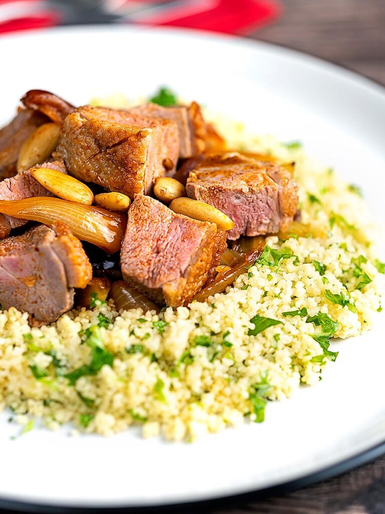 Portrait image of a duck breast tagine with dates and almonds served on a bed of buttered couscous