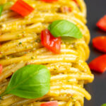 Portrait close up image of pesto alla trapanese served with spaghetti and tomato concasse and fresh basil with text overlay