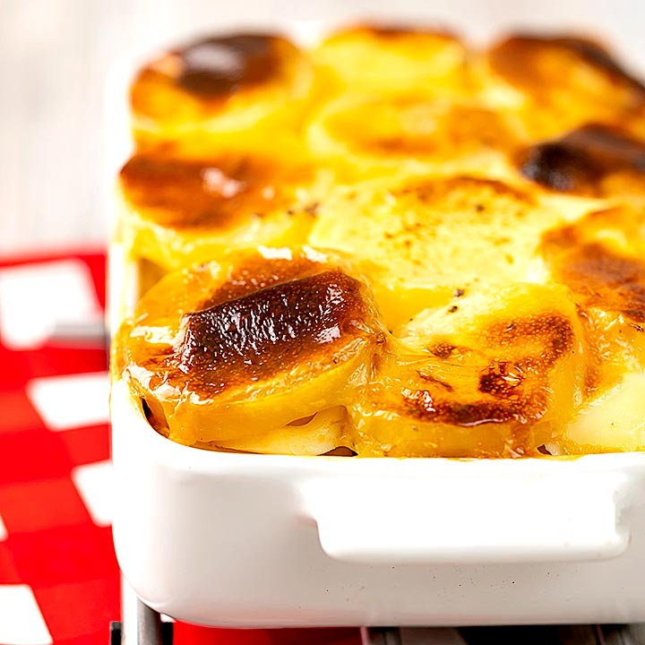 Square image of rakott krumpli or Hungarian layered potatoes served in a white gratin dish