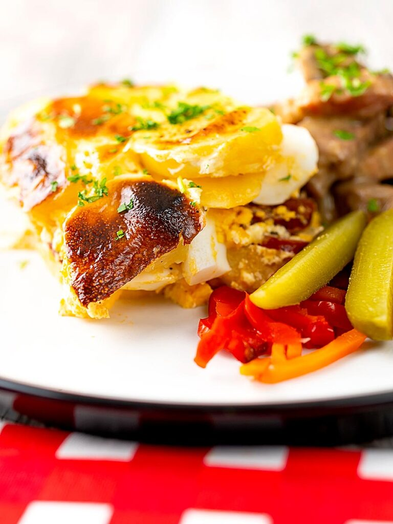 Portrait image of rakott krumpli or Hungarian layered potatoes served on a white plate with borsos tokany and pickles