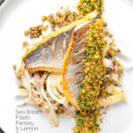 Portrait overhead image of pan fried sea bream fillet served with a parsley crumb and puy lentils with fennel with text overlay