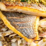 Portrait close up image of pan fried sea bream fillet served with a parsley crumb and puy lentils with fennel with text overlay
