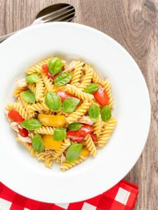 Portrait overhead image of spicy chicken pasta made with fusilli and roasted peppers served in a white bowl with fresh basil leaves