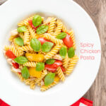 Portrait overhead image of spicy chicken pasta made with fusilli and roasted peppers served in a white bowl with fresh basil leaves and a text overlay