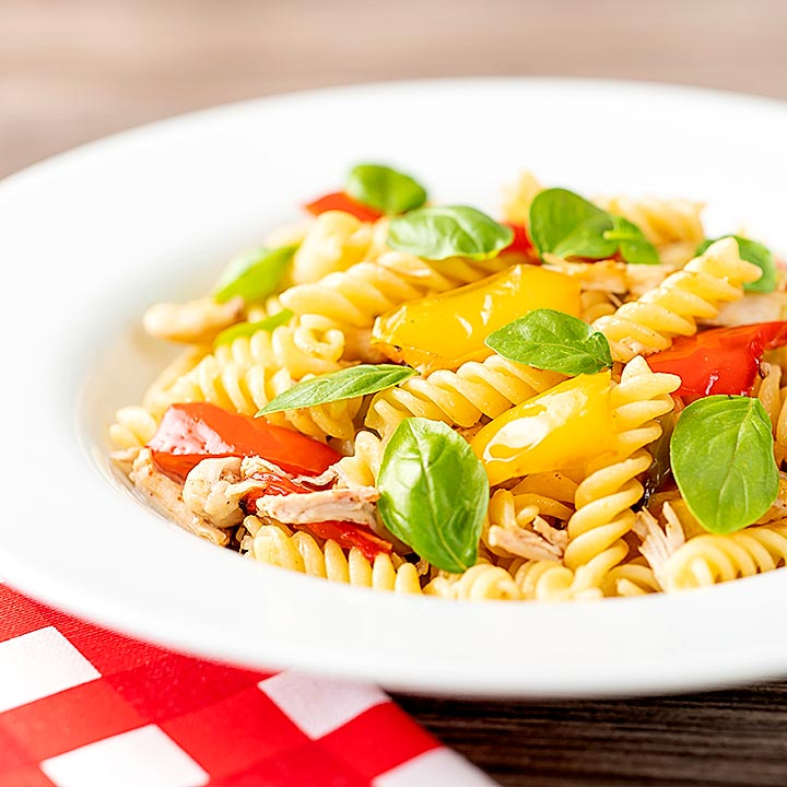 Square image of spicy chicken pasta made with fusilli and roasted peppers served in a white bowl with fresh basil leaves