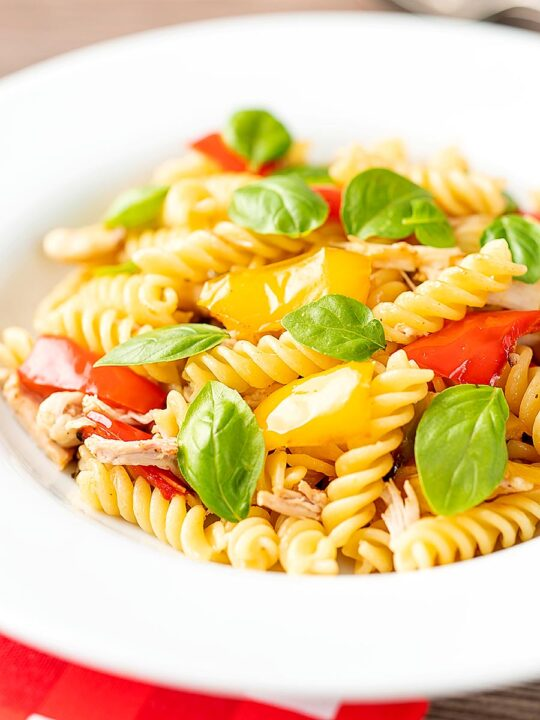 Portrait image of spicy chicken pasta made with fusilli and roasted peppers served in a white bowl with fresh basil leaves