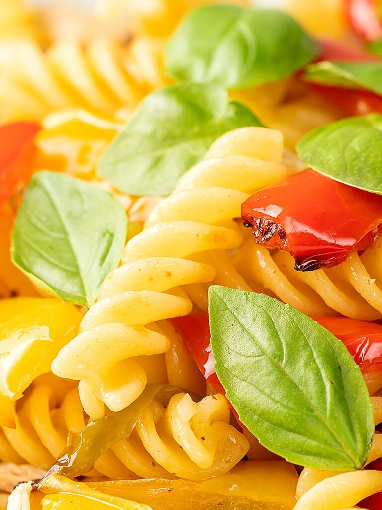 Portrait close up image of spicy chicken pasta made with fusilli and roasted peppers served with fresh basil leaves