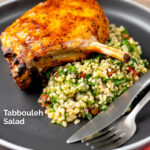 Portrait image of a herby tabbouleh salad served on a dark plate with a harissa glazed pork chop