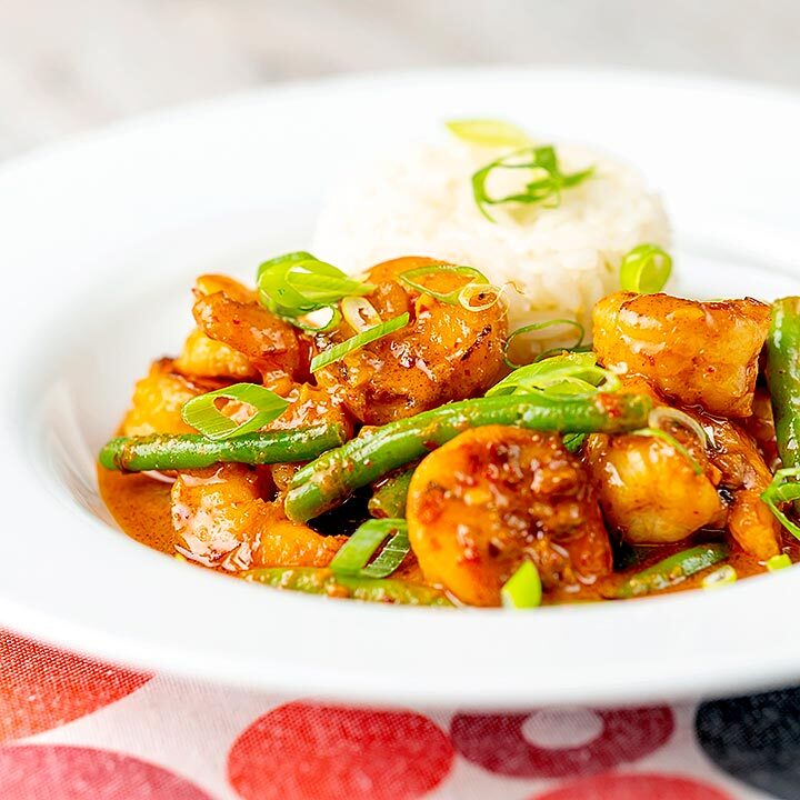 Square image of a Thai red prawn curry with green beans served in a white bowl with green onions and jasmine rice