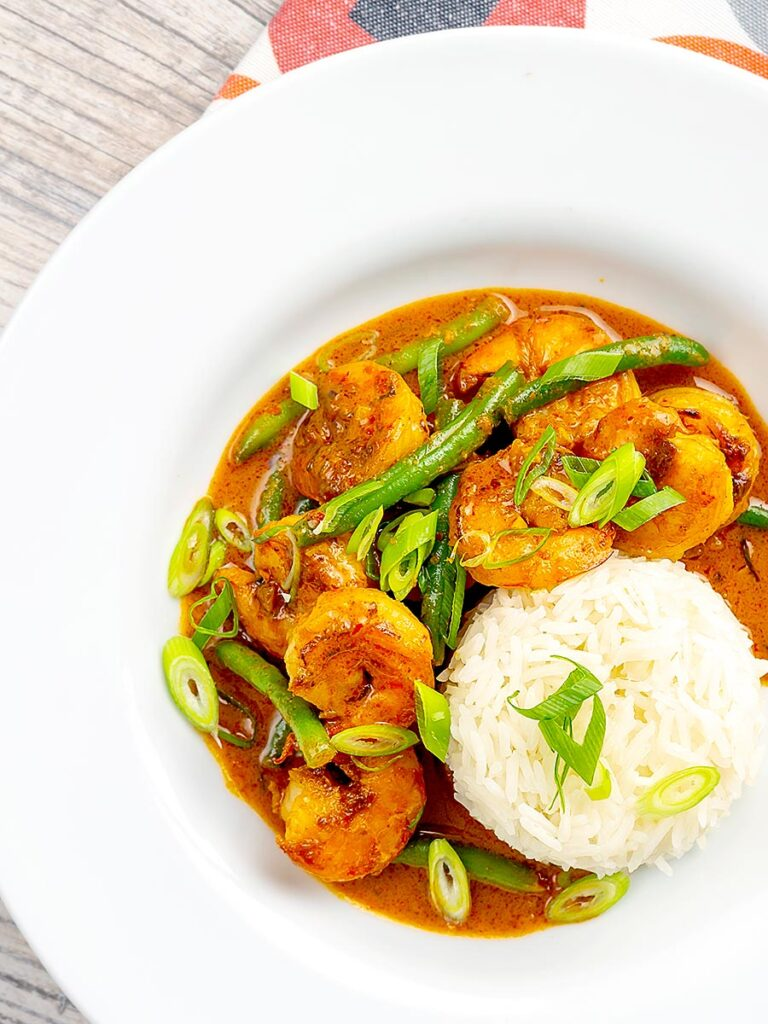 Portrait overhead image of a Thai red prawn curry with green beans served in a white bowl with green onions and jasmine rice