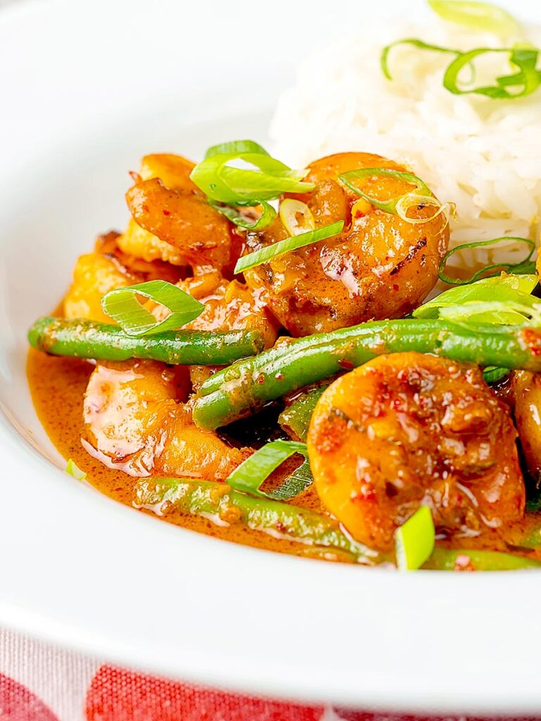 Portrait image of a Thai red prawn curry with green beans served in a white bowl with green onions and jasmine rice
