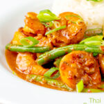 Portrait image of a Thai red prawn curry with green beans served in a white bowl with green onions and jasmine rice with text overlay
