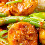 Portrait close up image of a Thai red prawn curry with green beans served with green onions with text overlay
