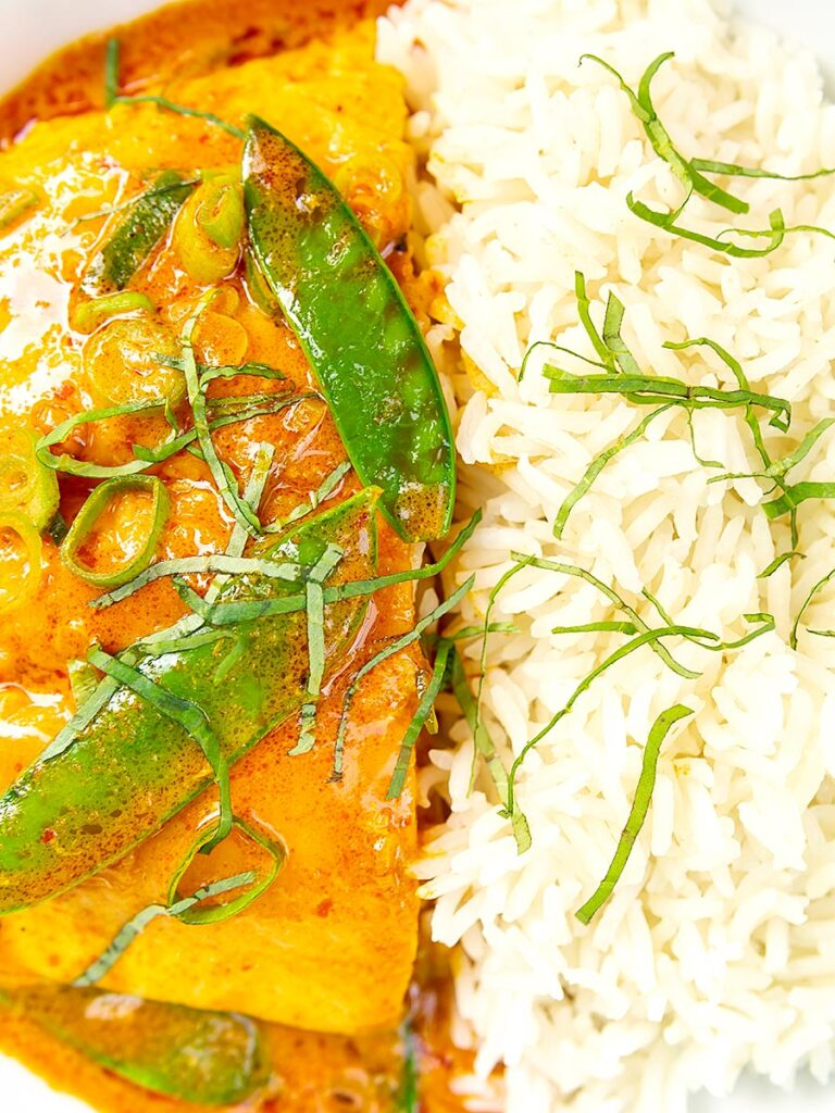 Portrait overhead close up image of a red Thai salmon curry with mangetout peas and shredded Thai basil served with jasmine rice
