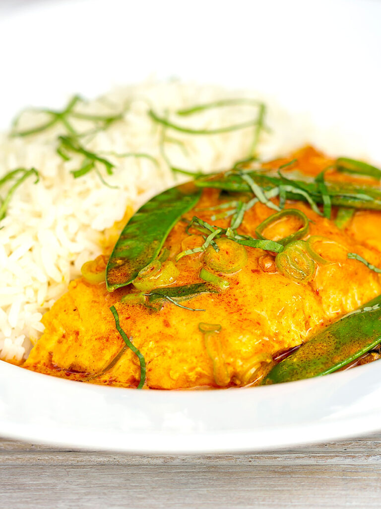 Portrait image of a red Thai salmon curry with mangetout peas and shredded Thai basil served with jasmine rice
