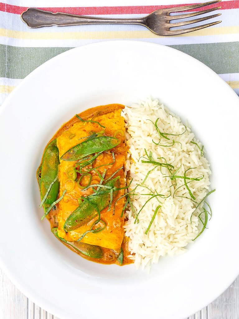 Portrait overhead image of a red Thai salmon curry with mangetout peas and shredded Thai basil served with jasmine rice