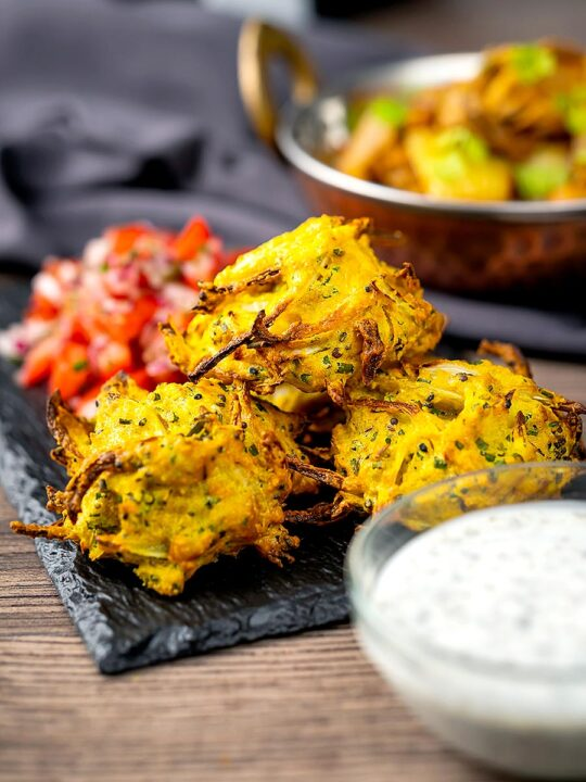 Portrait image of crispy air fryer onion bhaji or pakora served with a curry and mint and yoghurt dip