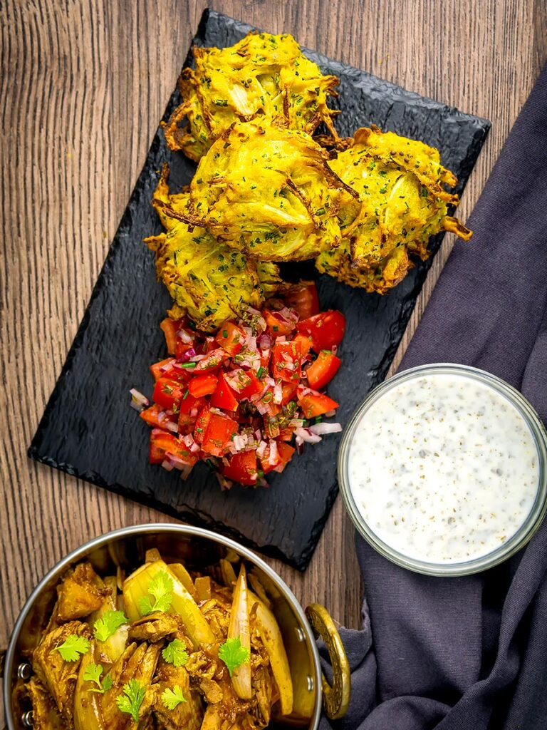 Portrait overhead image of crispy air fryer onion bhaji or pakora served with a curry and mint and yoghurt dip