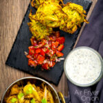 Portrait overhead image of crispy air fryer onion bhaji or pakora served with a curry and mint and yoghurt dip featuring a text overlay