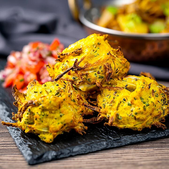 Square image of crispy air fryer onion bhaji or pakora served with a curry and mint and yoghurt dip