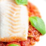 Portrait close up image of cod fillet baked in tomato sauce served on a white plate with a text overlay