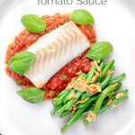 Portrait overhead image of cod fillet baked in tomato sauce served with green beans amandine on a white plate with a text overlay