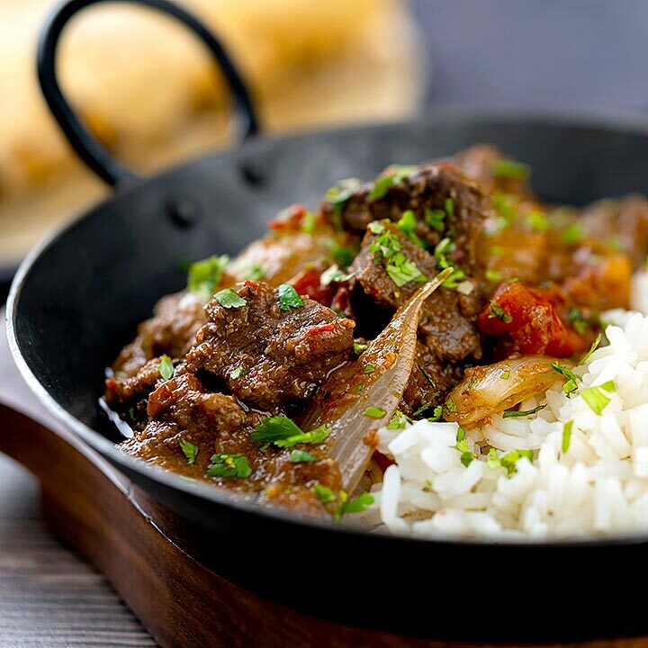 Square image of an onion rich beef dopiaza curry served in an iron karahi with rice and a coriander garnish